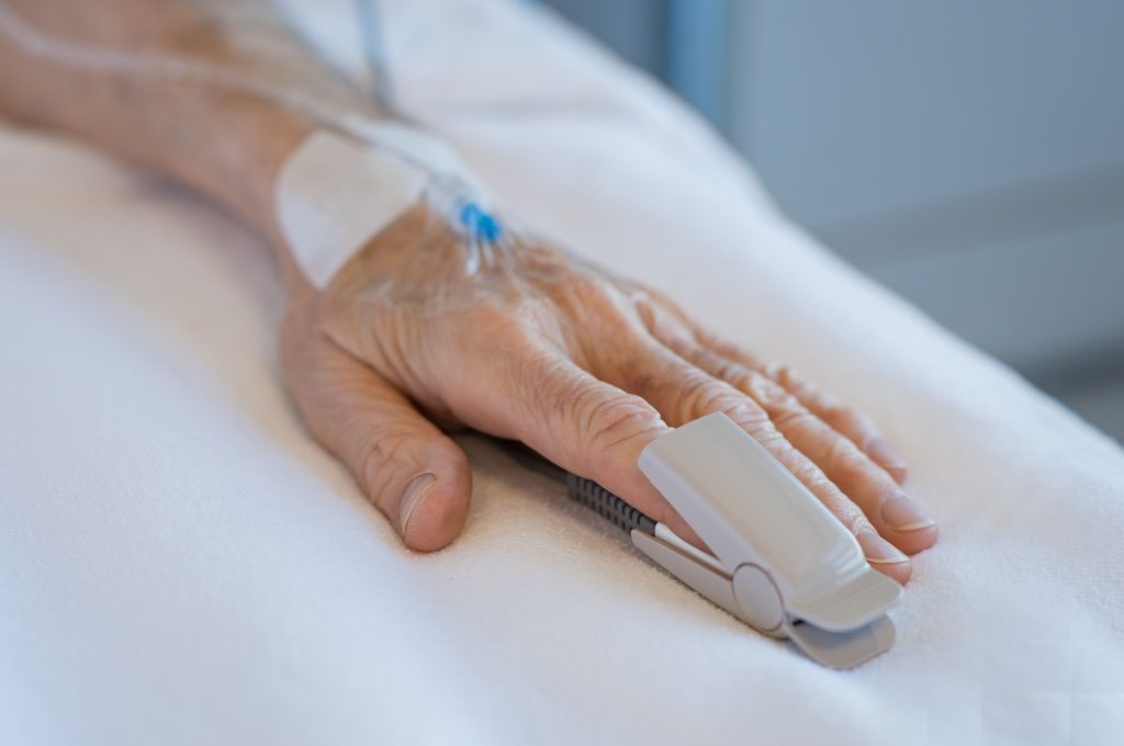 PAtient's hand on hospital bed, with syringe. family's medical negligence rights