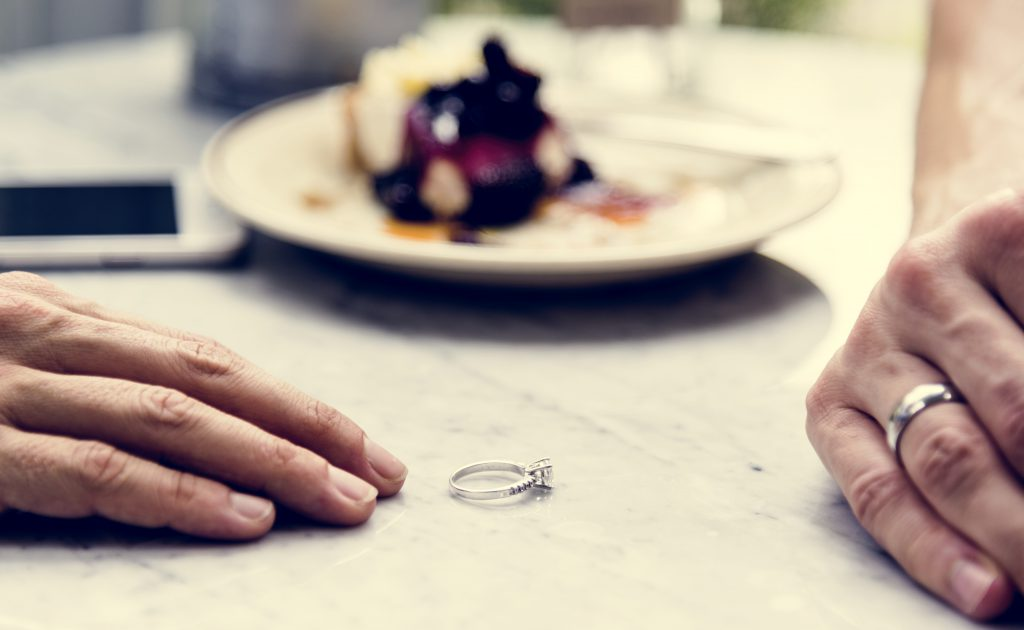 Calling Time On Our Marriage - couple's hands and woman's wedding ring on table