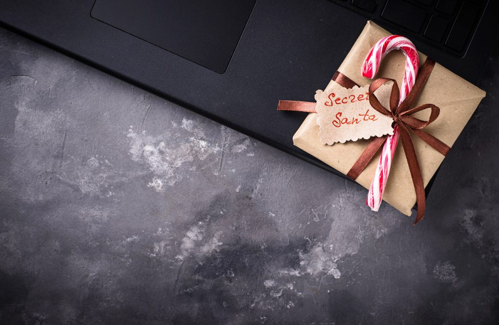 secret Santa gift sat on a laptop. From blog post titled Planning A Christmas Night Out When You're Self Employed