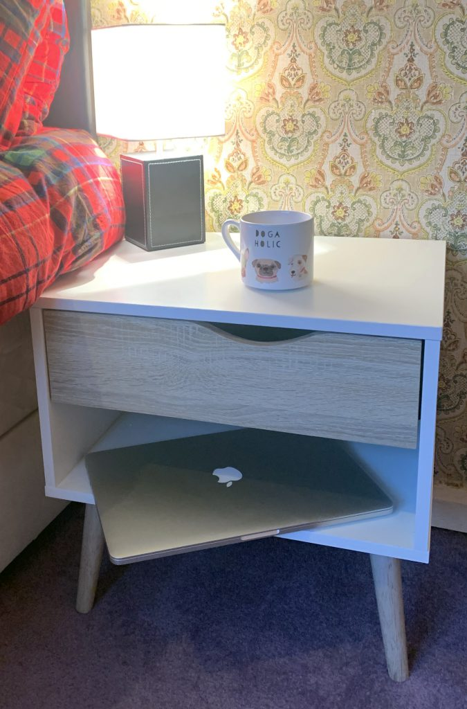 Vonhaus light oak and white bedside table - with a laptop, cup of tea and lamp on top.