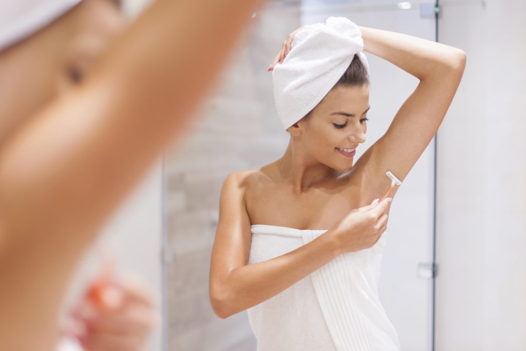 woman shaving armpit in bathroom with towel on her head.