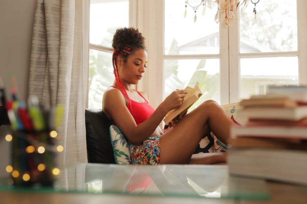 African American Woman Reading Book At Home Near Window - Ways to make more time for yourself