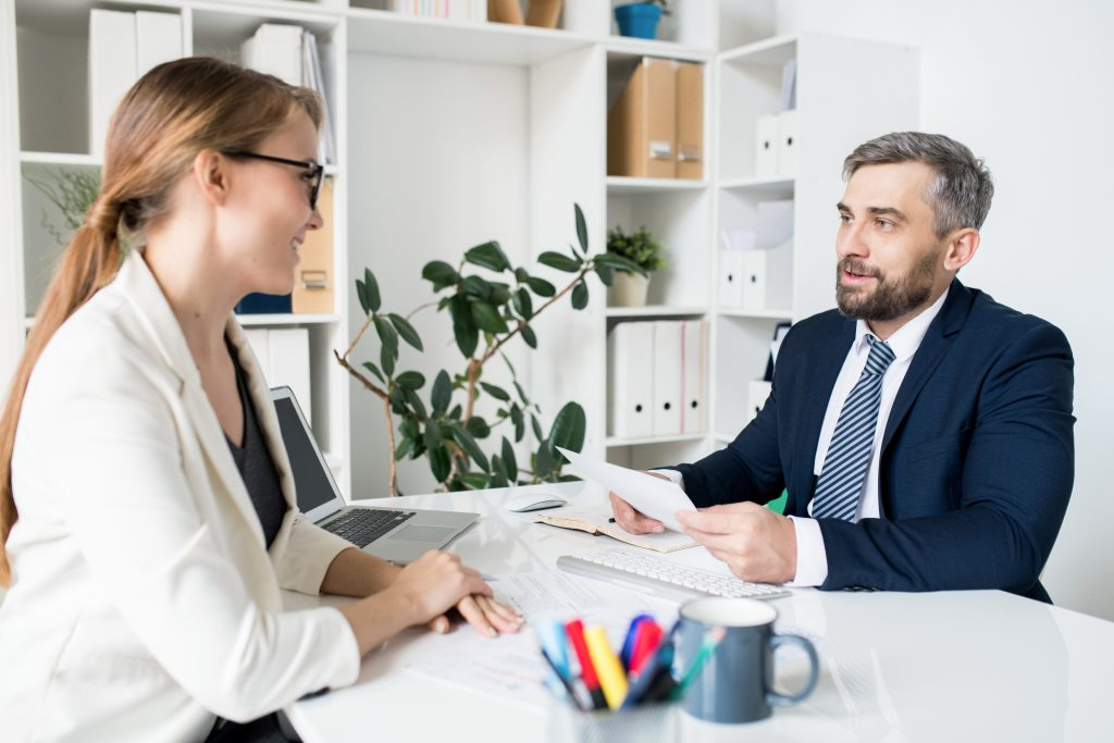 Content handsome HR manager in formal jacket sitting at table with computer and reading resume of job candidate while interviewing her at meeting in office