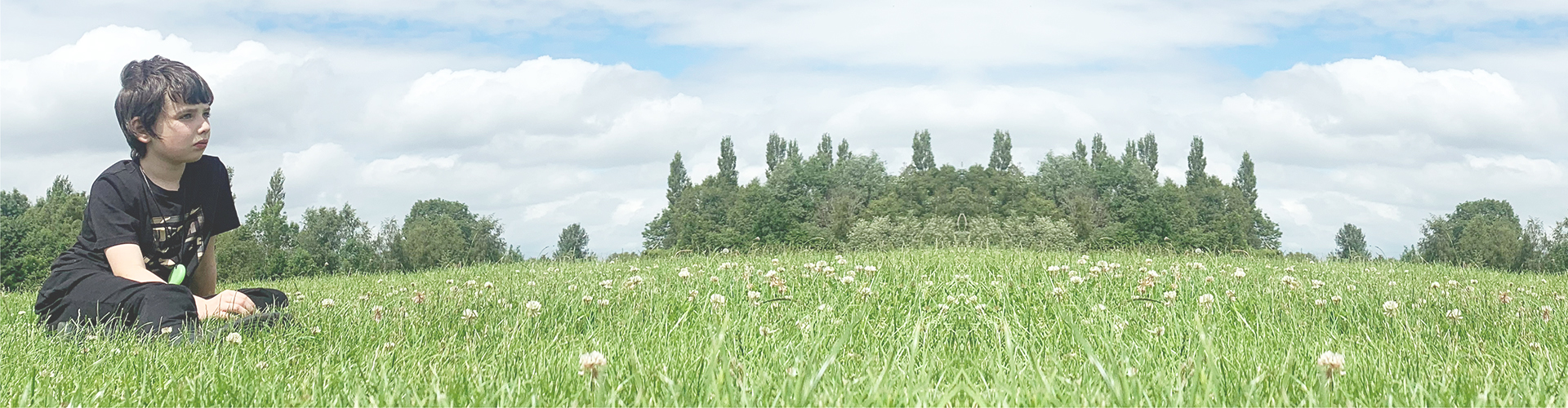 Sam sat on a field, staring out at the sky
