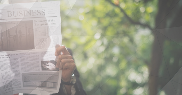 Man Reading Financial News Reports to Gather Economic Indicators
