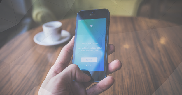 Top Trading Twitter Accounts - Man Holding Phone Using Twitter