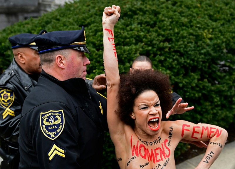 Topless protester gets close to Bill Cosby as retrial begins