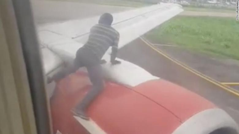 Man jumps on plane wing as it prepares for takeoff