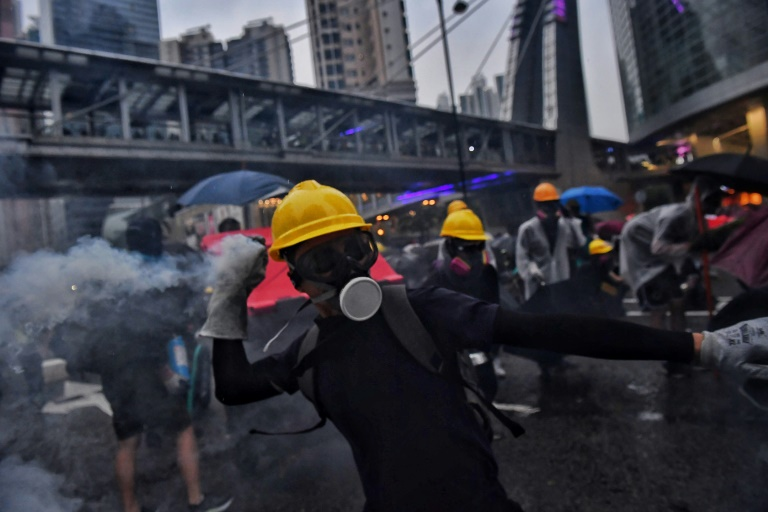 Hong Kong police say radical protesters forced use of water cannon, warning shot