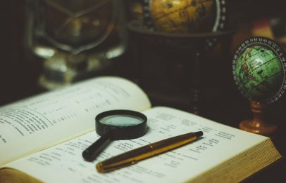 A photograph of a magnifying glass and pencil laying on an open book