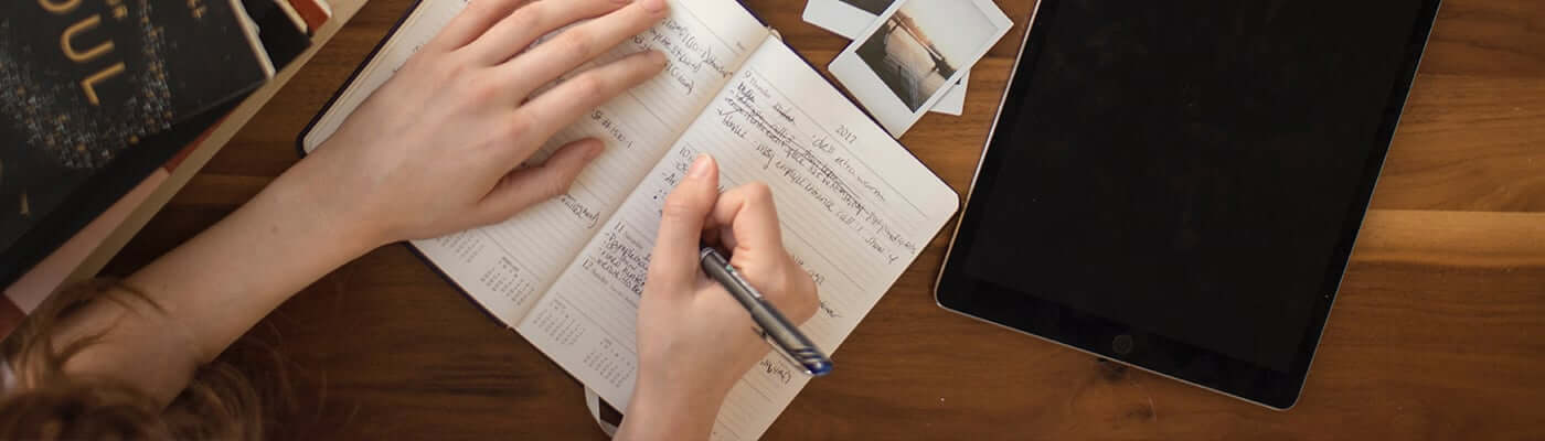 A photograph of a woman writing in a notepad