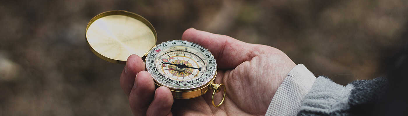 Photograph of a hand holding a compass, with the compass pointing north west