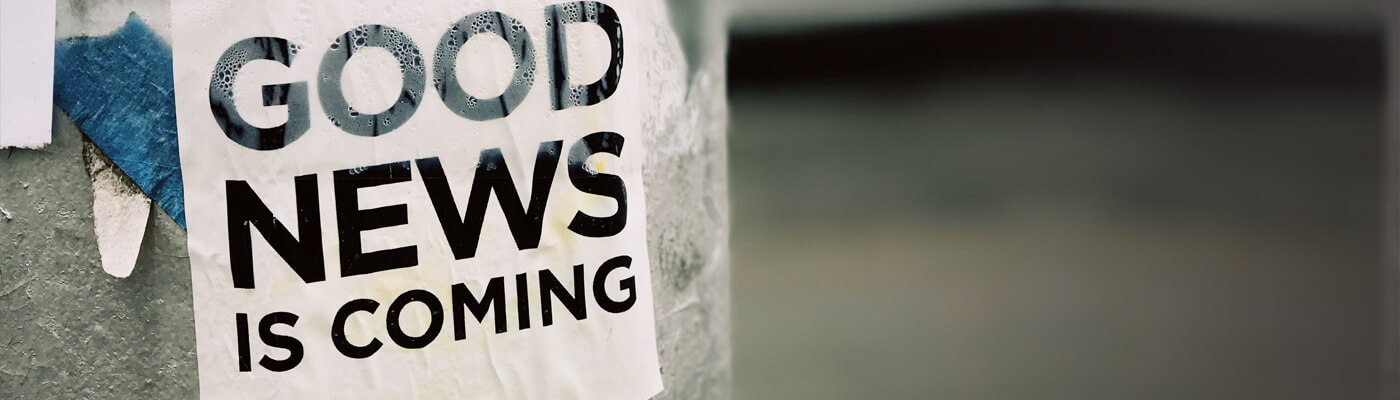 "Photograph of a lamp post, with a sign reading the words ""Good news is coming"""