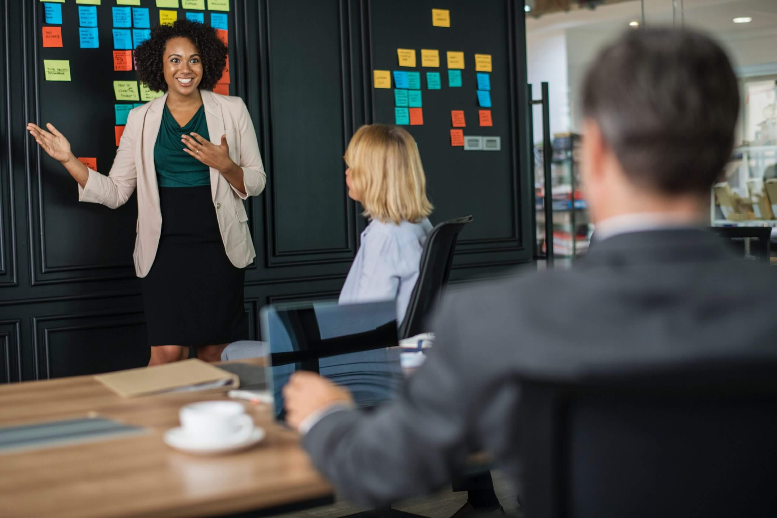 businesses achieving digital solutions - marketing meeting with woman holding hand up and smiling toward blackboard of post-it notes