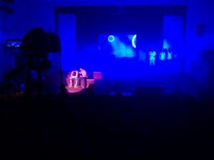 Low lighting theatre show with a spotlight placed on two actors sat on stage performing.