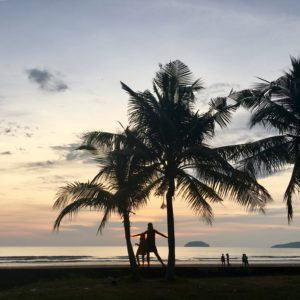 People standing between two trees on a each in Borneo. The sun is quite low and you can see an island offshore.