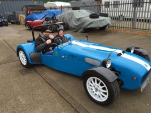 Constructed Lotus 7 kit car with two people sat in it