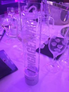 Engage Trophy for Best use of technology and Best use of training displayed on a clothed table with wine glasses