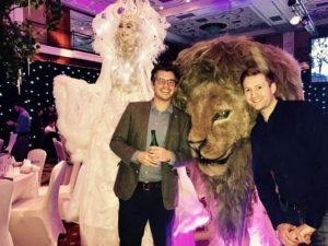 Posing with a with and a Lion with at an indoor venue with a bottle in hand
