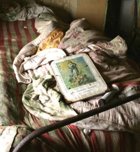 Artistic shot of an old bed with an old dirty mattress, covers and book on it.