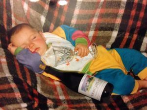 Sleeping infant in a colourful baggy onesie holding a glass and resting against a bottle of wine.