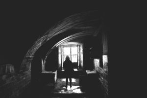 Image of someone standing in a dark Patarei prison cell. The hard floor has puddles of water illuminated by a window.