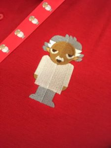 Close up of Albert embroidered onto a red polo shirt