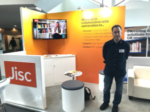 Jisc stand featuring a T.V and some stalls