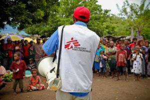 Person wearing a Medecins Sans Frontières shirt standing in front of a community with a megaphone