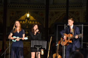 Music theatre stage with three vocalists playing the ukulele, tambourine and acoustic guitar from left to right.