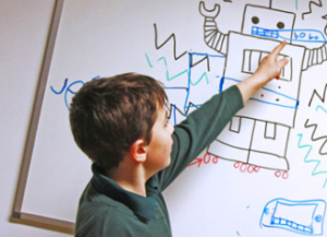 A BrightSparks child pointing to a whiteboard drawing of a robot at MakerClub at Barclays Eagle Lab Brighton
