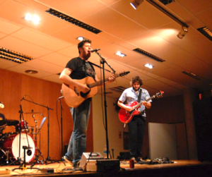 Two people playing the guitar on stage with a drum set in the background.