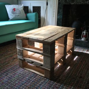 Do it yourself carpentry coffee table on a rug next to a sofa and disused fire place.