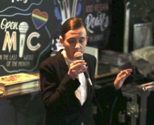 Singing in suit with a chalk board in the background. Open mic is written on the board with a rainbow pride heart.