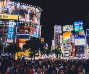 Tokyo city at night featuring people walking around being overshadowed by many large bright billboards and signs