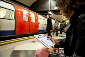 Person sat on a London Underground platform using a tablet with a tube train arriving in the background