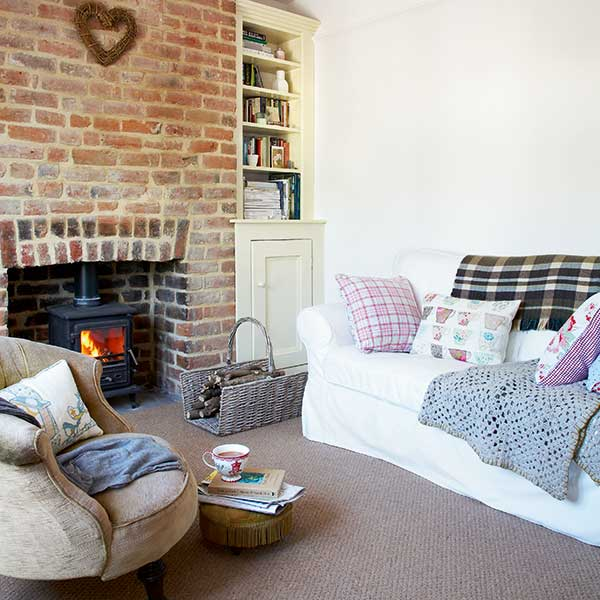 cosy living room in a cottage with exposed brick and woodburning stove