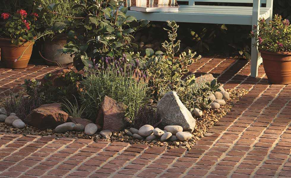 Bradstone Carpet stones in rustic red with scottish cobbles and harvest gold decorative aggregate on patio with bench