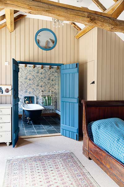 listed barn conversion bedroom to ensuite with blue door