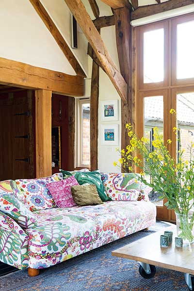 listed barn conversion pattern sofa by window