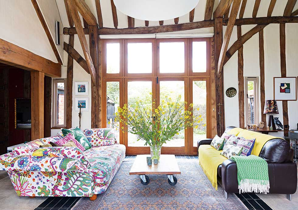 listed barn conversion floor to ceiling windows with beams in double height living room
