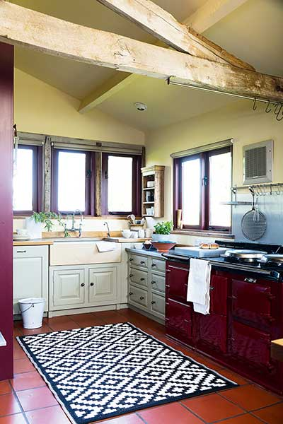 listed barn conversion kitchen with red aga and blue cabinets