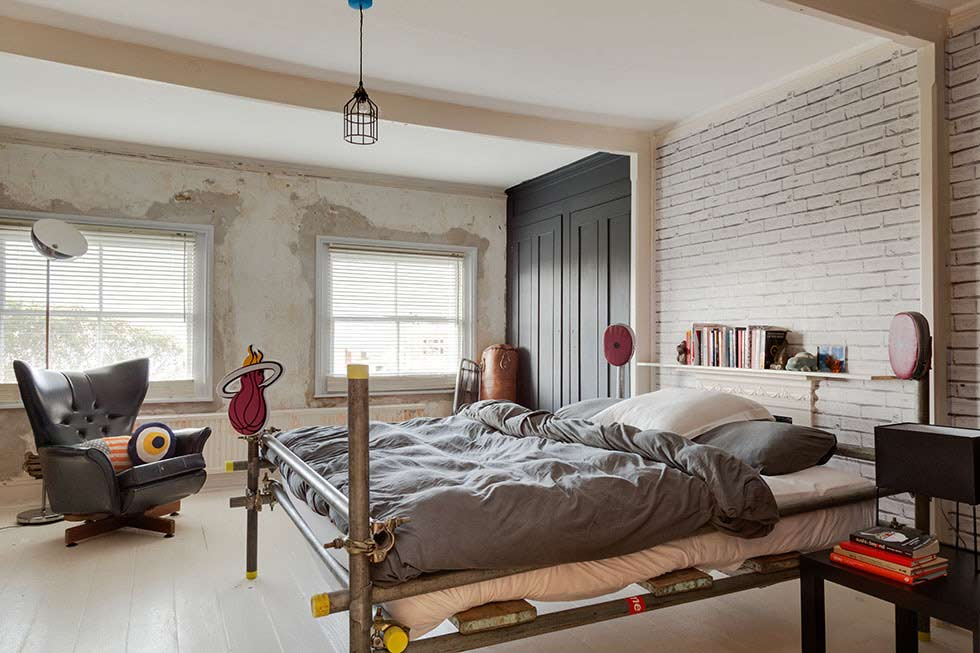 New York loft style bedroom in an otherwise colourful victorian villa