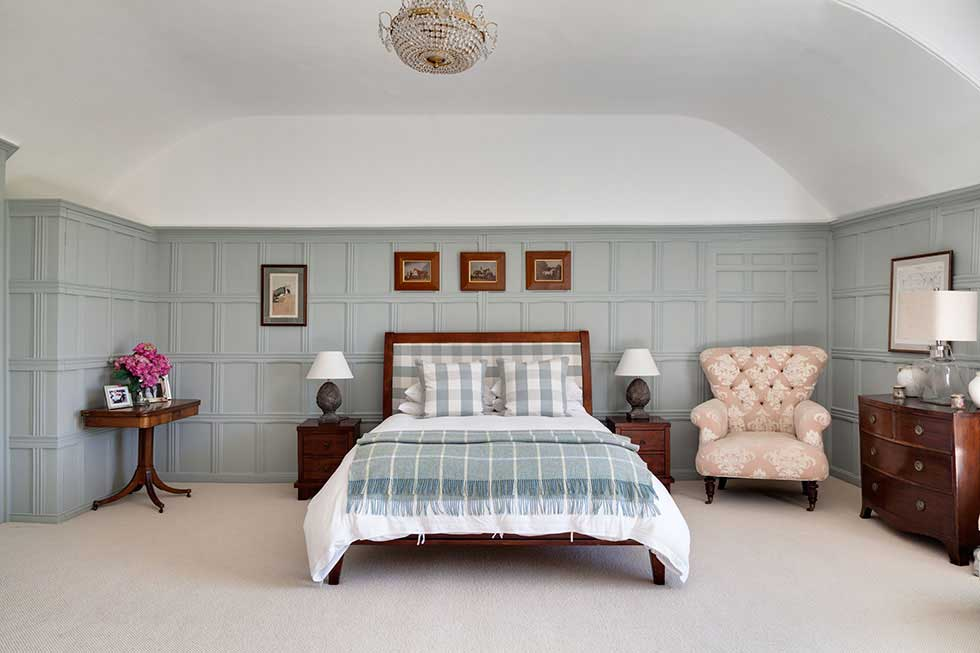 a green panelled bedroom with country style furnishings
