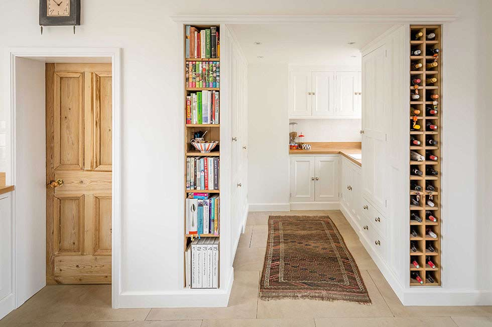 clever alcove wall storage with a book shelf and wine store