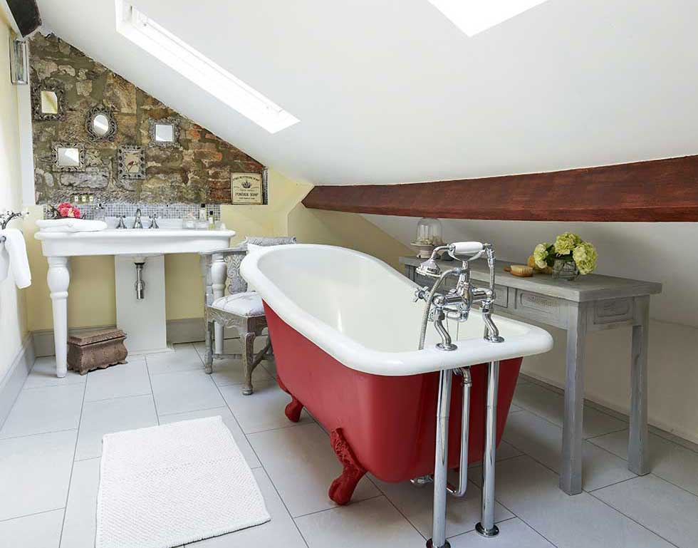 red slipper bath in a stone cottage loft bathroom
