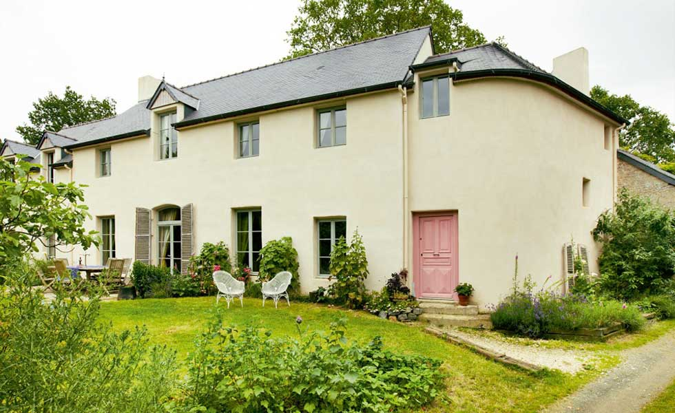 large white farmhouse with grey roof, light green window frames and pink side door