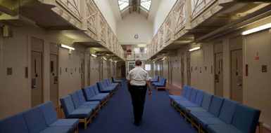 A female prison officer walks through the communal area inside one of the residential wings. HM Prison Styal is a Closed Category prison for female adults and young offenders, located in the village of Styal (near Wilmslow) in Cheshire, England. The prison is operated by Her Majesty's Prison Service. Styal is a Closed Category prison for sentenced and remanded female adults and young offenders. There are also facilities for mothers with babies up to age 18 months. The education provision at Styal is contracted out to The Manchester College. Courses offered include hairdressing, information technology, art and design, ESOL, catering, industrial cleaning, painting & decorating, and Open University support. | Location: Wilmslow, England, UK.