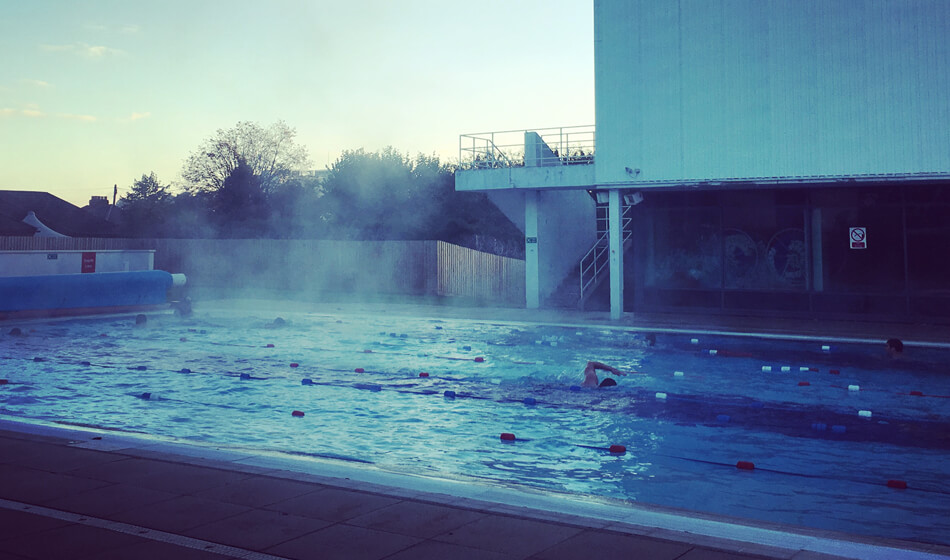 Outdoor lane swimming. Steam coming from water in early morning swim.