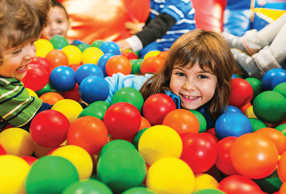 Children in soft play ball pit having fun